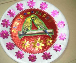 This plate is decorated with paper flowers. stone aarthi plate & www.iKolam.com