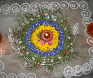 Rangoli: Karthigai decoration with arugampul, sangupoo & yellow poo.