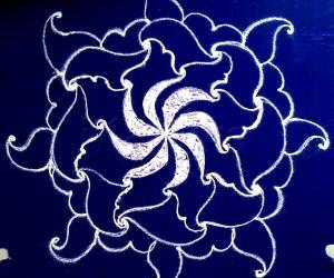 White swirling flower- a freehand rangoli with kolamavu on a blue plastic cover.