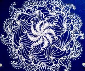 Rangoli: White swirling flower- a freehand rangoli with kolamavu on a blue plastic cover.