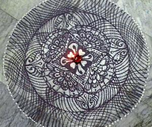 A freehand rangoli with recycled dark blue colour.