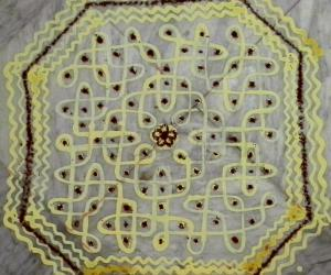 Rangoli: Chikku kolam with rice batter mixed with haldi. Dot count 11 dots 3 lines till 3  straight dots.
