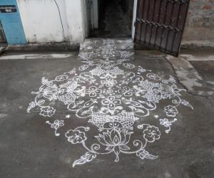 Rangoli:  Fishes on lotus. Kolam in white.