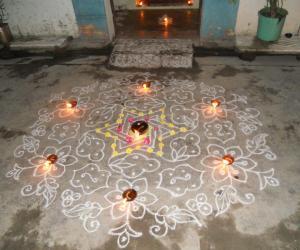 Karthigai kolam in white with deepam & flowers.