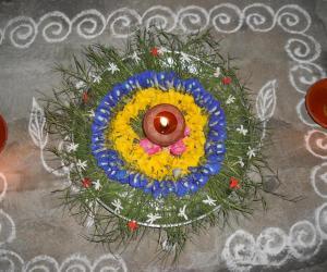 Rangoli: Karthigai decoration with arugampul, sangupoo & yellow poo.