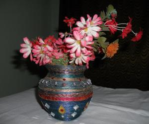 Clay pot craft with silk thread as flower vase.