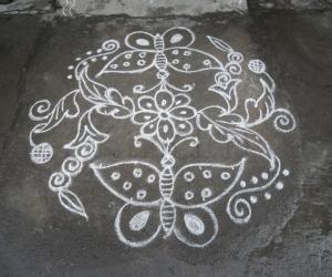 Rangoli: A small butterfly kolam in white.