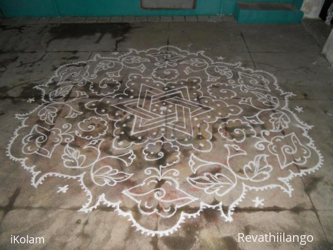 Rangoli: Star & bitterguard kolam in white.